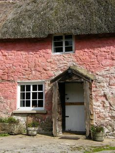 An unusual pink thatched cottage in the small village of Ponsworthy on Dartmoor, Devon.