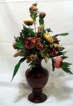 "Floral Arrangment Ranunculus & Pepper Berries Burgundy metal vase with multi colored Ranunculus flowers accented with rose pepper berries. 20""Hx10""W"