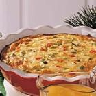 1 medium onion, chopped  1 medium green pepper, chopped  1 garlic clove, minced  2 tablespoons butter or margarine  1/2 cup chopped tomatoes  1/4 cup minced fresh parsley  5 eggs, lightly beaten  2 cups shredded mozzarella cheese  1/2 cup soft bread crumbs