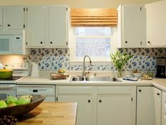 A vintage vinyl tablecloth in a blue-delft pattern is used to make this charming backsplash. Again, the possibilities are endless as far as pattern and color, and the materials are very affordable.