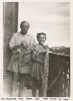 Pablo Picasso holding a dog and standing on a balcony with his daughter Maya Ruiz-Picasso.