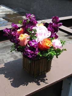 Sunny roses pop against purple and pink hues in this vibrant unique floral centerpiece