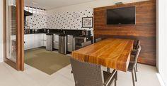 O escritório de arquitetura e interiores Conseil Brasil assina o projeto que traz uma ampla sala de almoço com painel de madeira e televisão.