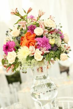 Elegant colorful tall floral centerpiece idea - clear glass vase filled with bright pink, orange and ivory flowers {Andrea Helfer Photography}