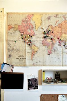 world map with pins to mark where you've traveled + decorate with postcards, ive always wanted to do this! (Sans postcards)