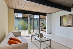Modern living room opens to atrium with slanted wood beamed ceiling