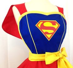 Delivering truth, justice and the American Way - Super Girl is here! Super Girl is a super chic apron with its fitted blue bodice (with yellow piping along princess lines to accent your curves), sweetheart neckline and trimmed in yellow bias. The bodice features the Superman/girl logo in vinyl and is fully lined for extra durability and protection from spills. Super Girls red cape makes an easy escape from the apron, and may make flying around your next party easier. It is edged in matching…