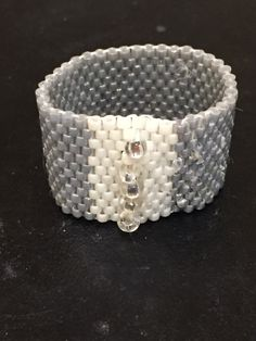 Silver and ivory delica seed beads size 11 makeup the simple peyote stitch ring.  Five size 8 glass beads were added to the center.  Rings are a quick project for the novice beading student.  I enjoyed making the ring.