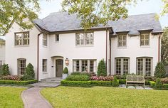 This entire house is gorgeous, but I especially love the simple landscaping out front. That's what I envision! Boxwood borders with evergreen arborvitae and colorful annuals in the garden beds.   Color Outside the Lines: Houston House Envy