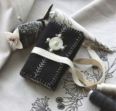 Janette Needlebook Pattern, This classy little tri-fold needlebook is felted wool on the outside, lined in fabric, and tied with a cotton twill ribbon. The simple embroidery secures a mother of pearl button and pearl beads to the cover, and embellishes the whimsical pincushion. $10.00