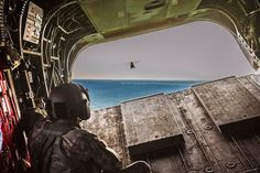 Flight engineer Sgt. Trenton Martin, Company B, 2nd Battalion, 3rd Aviation Regiment, 3rd Combat Aviation Brigade watches from the ramp of a CH-47F Chinook helicopter.