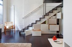Space beneath the stairs should be put to work in a compact space, and what better way than with perfectly fitted storage compartments? An open-sided, rather than walled-in, staircase keeps a small room feeling more spacious and allows light into the upper level.