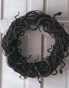 Cute! Grapevine wreath (thick is better), rubber snakes of various shapes and sizes, a few cans of black spray paint, glue gun or wire for anchoring, and small bottles of red and green craft paint.   Spray paint everything black, weave the snakes in place, wire/hot glue where anchoring is needed, then do another light coat of spray paint (to cover wire/glue). To add dimension, go back and re-paint forked tongues red and eyes green. by runyonwiggins