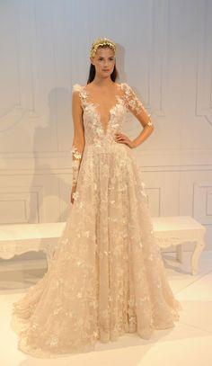 Vestido de noiva Galia Lahav é inspirada na realeza com decote profundo e manga comprida transparente com aplicações de flores em relevo. Acinturado, o modelo todo tem aplicações de flores e é rendado.