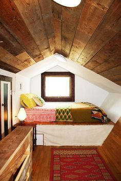 There's something gorgeous and charming about a square window in a tiny loft room like this. So cozy!