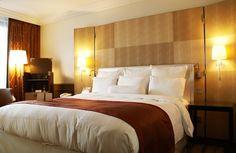 Modern cozy bedroom w/ sconce lighting, rust coverlet & tan checked fabric headboard - Homeclick Community