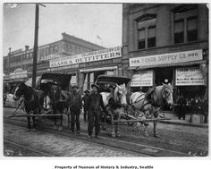 1898 - Two delivery carts wait outside gold rush outfitters on First Avenue near Madison Street in downtown Seattle. They will carry goods to the waterfront to be loaded onto ships heading north to the Alaskan ports that served the Klondike gold fields.