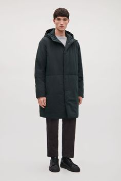 A padded style, this hooded coat is made from a smooth technical material with a silky lining. Designed for a long length, it has concealed inner pockets, hidden press-stud fastenings, a zip-up front and discreet side and inner pockets.