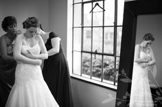 Anna and Spencer Photography, Atlanta Documentary Wedding Photographers. Mother and bridesmaid helping the bride in to her wedding dress.