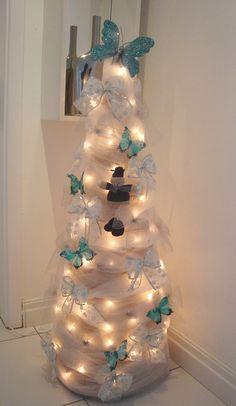 Um cone de papelão é a base desta árvore. O revestimento de tule ganhou decoração de luzes, laços e borboletas. Lucirene Bitelo, integrante da comunidade Casa Claudia, usou o azul para combinar com a decoração de sua casa.