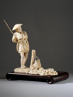 """IVORY OKIMONO Meiji Period Depicting a fisherman with a pole and basket, casting his line into the sea. Detailed carving. Signed """"Nippon Tokyo Udagawa Sei"""". Height 10.5"""" (26.67 cm)."""