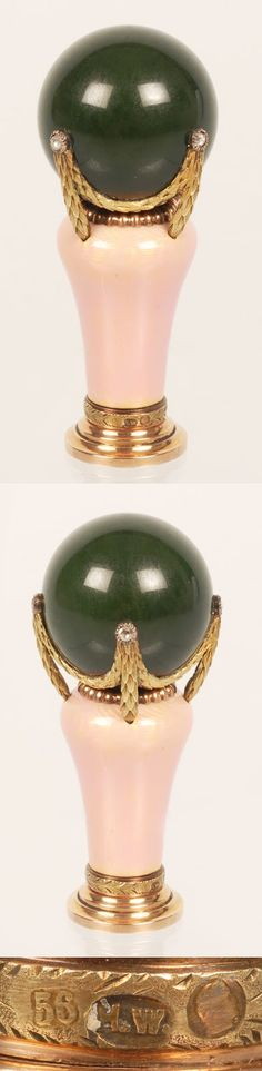 Faberge's parasol handle. Made by workmaster Henrik Wigström, sometime between 1908 and 1917. The parasol handle is covered in translucent pink enamel over a wavy guilloché ground. The green ball on top is carved out of nephrite and mounted with gold laurel swags set with diamonds. A gold chased band of laurel also encircles the bottom. The hight of the handle is 2 3/4'' (7 centimeters)
