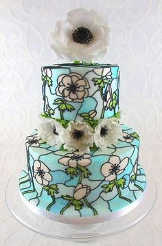 Anemone themed stained glass wedding cake. This is a display cake for this springs wedding fayres. The sugar flower on top is wired with seed head stamens and the ones on the middle of the cake are totally edible. The flowers on the cake where drawn on free-hand using pictures of real flowers for reference and painted on using edible dusts and gels mixed with confectioners glaze.