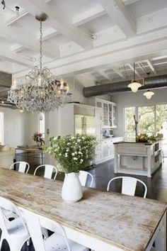 Kitchen with solid island, nice use of space, beams and chandelier look nice
