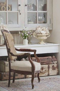 What a pretty little sitting area...I love the vintage suitcases piled under the built in cabinet