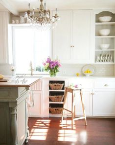 Cottage style kitchen with wood island, white cupboards, marble counters and chandelier