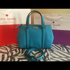 """Kate Spade Small Loden Bag 100% Authentic.  Color: Neon Turquoise.  Made of cross hatched saffiano leather.  Matching leather handles with long adjustable strap.  Gold plated hardware and protective feet.  Zipper and magnetic closure.  Side snap fasteners. Interior fully lined, includes zip pocket and two slide pockets. Measurements: 14.5"""" L x 9.5"""" H x 5.5"""" D. kate spade Bags Satchels"""