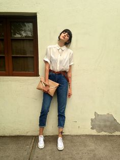25 Ways to Make Mom Jeans Look Modern | crisp white short sleeve button-down, belted + cuffed mom jeans, a tan leather envelope clutch, and white Chuck Taylor's | StyleCaster