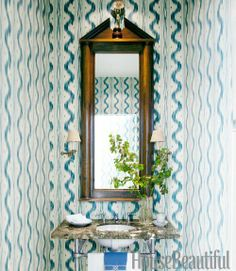 Pierre Frey Toile de Nantes ikat wallpaper in shades of blue cover the walls of a small powder room