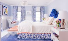 Blue walls, printed blue curtains, blue headboard, white bedding with red trim, printed blue bed skirt, blue rug, clear chandelier, light blue chair, white nightstand, and silver lamp