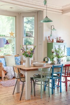 Lovely bright country kitchen...love the different coloured chairs