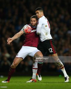 Andy Carroll of West Ham United challenges for the ball with Chris Smalling of Manchester United during The Emirates FA Cup, sixth round replay between West Ham United and Manchester United at the Boleyn Ground on April 13, 2016 in London, England.