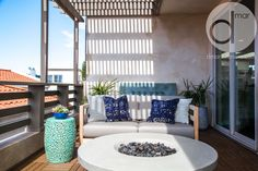 Outdoor living space, canopy, teak furniture, fire pit, water feature, balcony, blue throw pillows, ceramic stool, greenery