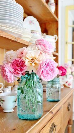 pink flowers in light blue mason jars