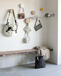 Wooden buttons as hooks over low bench in the entryway