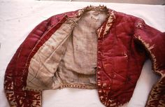 Extant doublet ca. 1560. Supposedly Italian. Now held in the Royal Museum of Scotland and documented/patterned by Janet Arnold. Red silk satin lined with linen, with cotton wool stuffed loosely between the vertical quilting. The doublet has six eyelets at each sleeve head for lacing on armor components and eyelets set into the narrow skirting for pointing (lacing) one's breeches to the doublet. . Photo credit Mary Westerman Bulgarella