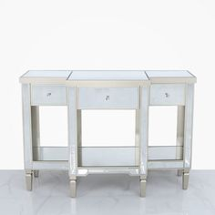The Georgia Silver 3 drawer console table features a fully mirrored tabletop and panelling throughout, 3 drawers with crystal handles, a lower shelf and champagne painted trims and legs Mirrored Console Table, Drawers, Wooden Trim, Mirrored Bedroom Furniture, Table, Beautiful Mirrors, Contemporary House, Console Table, Bedroom Chest Of Drawers