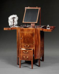 c. 1790 George III Period Mahogany Gentleman's Dressing Table by Gillows of Lancaster the divided shaped crossbanded top opening to reveal an adjustable rising mirror, bottle holders, a large moulded edge hole for a bowl and small holes for soap dishes etc. above a dummy drawer and a cupboard door to access the water jug, all above a pull out bidet formed as two dummy drawers on legs and still retaining the original white Wedgwood bidet.