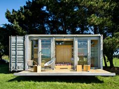 port a bach shipping container retreat by atelierworkshop - the compact dwelling employs a single shipping container which comfortably accommodates two adults and children.  the interior features built-in cupboards and shelves which offer ample storage space, a stainless steel kitchen and bathroom with open shower,  sink and composting toilet - expressing the design's efforts to be environmentally clean.