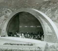 """The Hollywood Bowl opened in 1922, but didn't get its first shell until 1926, which is when this photo as taken. Along with its first shell, the Bowl also got its first permanent seating. Apparently, the acoustics of this shell were rather poor, so the next year Frank Lloyd Wright's son Lloyd Wright built a pyramidal shell out of leftover lumber from an earlier film production of """"Robin Hood."""""""