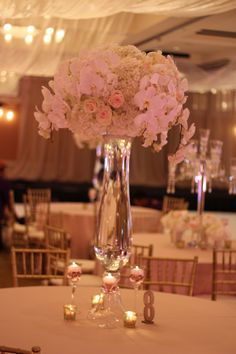 The altar will be flanked by tall clear fluted vases topped with a mound of cream hydrangeas, ivory spray roses, and white phalaenopsis orchids will flank the altar www.stemfloral.com