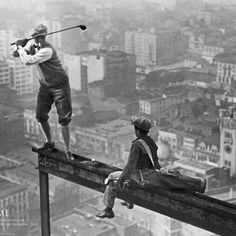 workers constructing a skyscraper take time off to eat lunch and play golf... on the skyscraper!!!