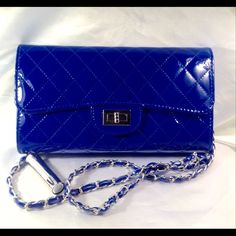 Royal Blue Handbag This quilted clutch bag is faux patent leather. Features a detachable blue and silver link strap, fully red lined with two compartments that include credit card slots and 1 slip pocket, exterior slip pocket, gold tone twist lock closure. Measures: 11 W X 6.5 H X 1.5 D (This closet does not trade or use PayPal ) Bags Clutches & Wristlets