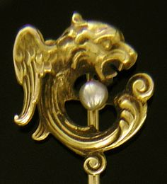 A fantastic winged creature with the head of a lion and body of a serpent coiled around a pearl. A nice example of the Victorian fascination with mythological and invented creatures.  The stickpin is beautifully detailed.  Crafted in 14kt gold,  circa 1890.