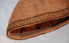 Reconstruction of a hat found in Birka. Made of light brown wool in six wedges. Every visible stitch is hand made with linen thread. The decoration was made with tablet weaving (100% wool). Lining of linen on the inside. The girth measure on the inside is 59,5 cm.