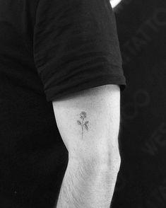 Fine line rose tattoo on the left upper arm.